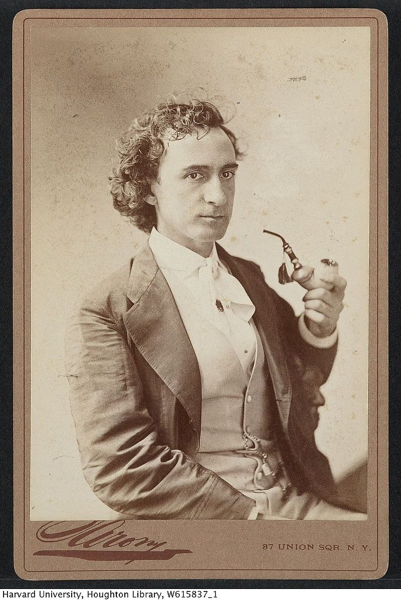 <b>Edwin Booth</b>     	</br>Cabinet card image of Edwin Booth, holding a pipe; dated 1867 by source.</br><br/><b>Source: </b><i>Public Domain TCS 1.2935, Harvard Theatre Collection. https://upload.wikimedia.org/wikipedia/commons/0/0d/Harvard_Theatre_Collection_-_Edwin_Booth_TCS_1.2935.jpg</i>